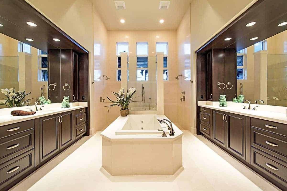 This is an elegant Beach-style primary bathroom with dark wooden cabinets and drawers on the two vanities flanking the bathtub in the middle of the beige floor leading to the large shower area at the far wall filled with beige tiles.