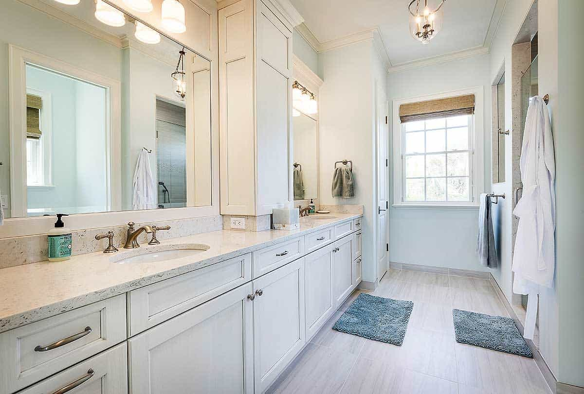 This simple and homey Beach style bathroom has a laid back feel to its light-hued walls and two-sink vanity that are warmed up by the yellow lights of the wall-lamps above the mirrors as well as the small semi-flush light from the ceiling.