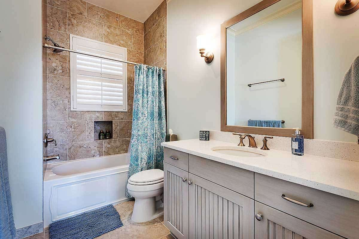 The wood-framed vanity mirror is flanked by two wall-mounted lamps with warm yellow lights that illuminate the white walls and ceiling complemented by the beige tiles of the flooring and shower area walls adorned with a green patterned shower curtain.