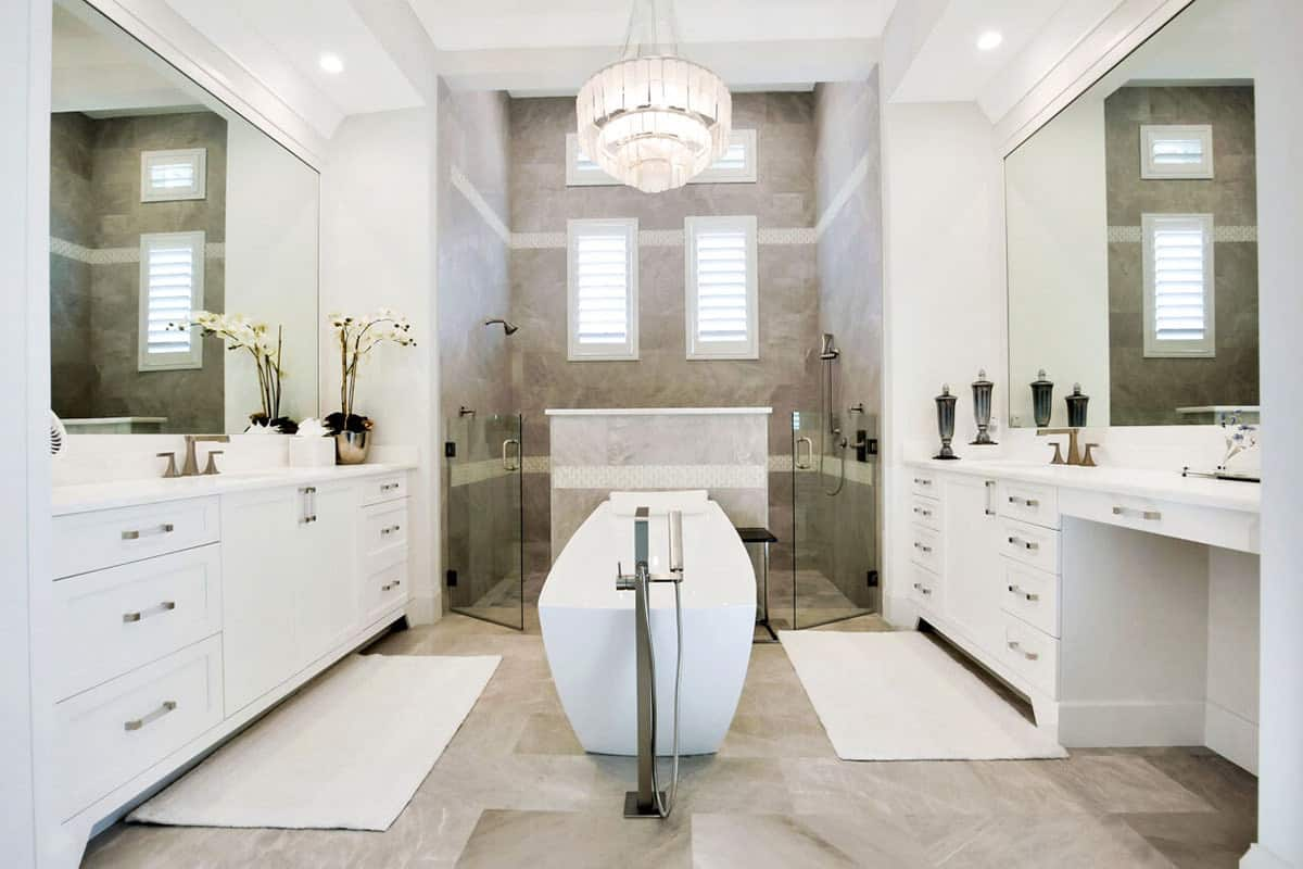 The gray marble flooring in the middle of the two white vanities is maximized by putting a narrow freestanding bathtub topped with an elegant pendant light coming from the white tray ceiling matching the shuttered windows of the shower area.