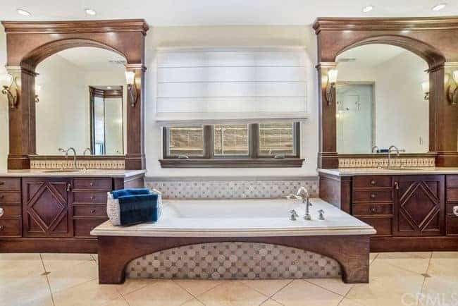 The large white bathtub is inlaid with a wooden housing that matches the flanking wooden vanities with elegant cabinets and drawers and wooden arches above that supports the vanity mirrors flanked by wall-mounted lamps.