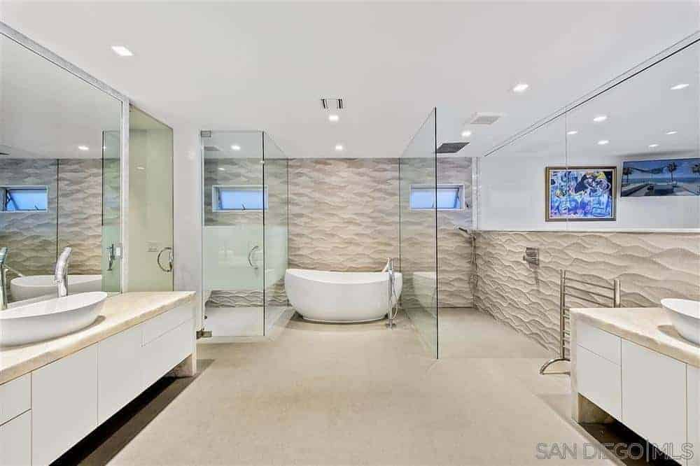 This wide and spacious bathroom has textured beige walls that look like sand paired with a light beige flooring that complements the white freestanding bathtub on the far wall flanked by two glass enclosed areas. One is for the toilet while the other is for the shower.