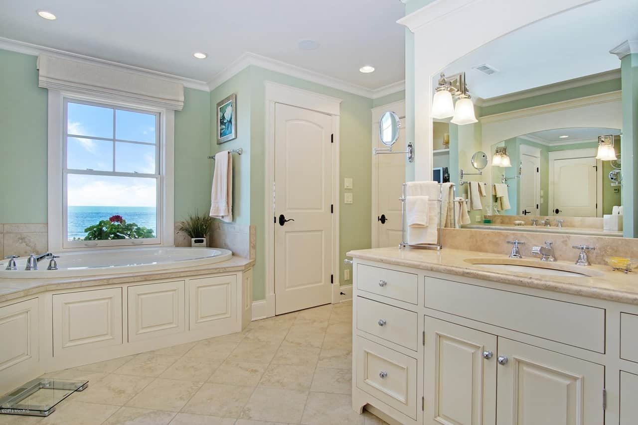This spacious Beach-style primary bathroom has a green hue to its walls that are mostly dominated by the combination of white and beige on the wooden vanity as well as the housing of the oval bathtub beneath the window.