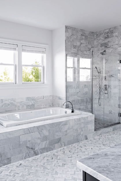 The white ceiling and bathtub are given a nice complex background filled with various patterns on the gray marble tiles housing the bathtub and the walls of the glass enclosed shower area beside it with the same herring bone flooring as the rest of the bathroom.