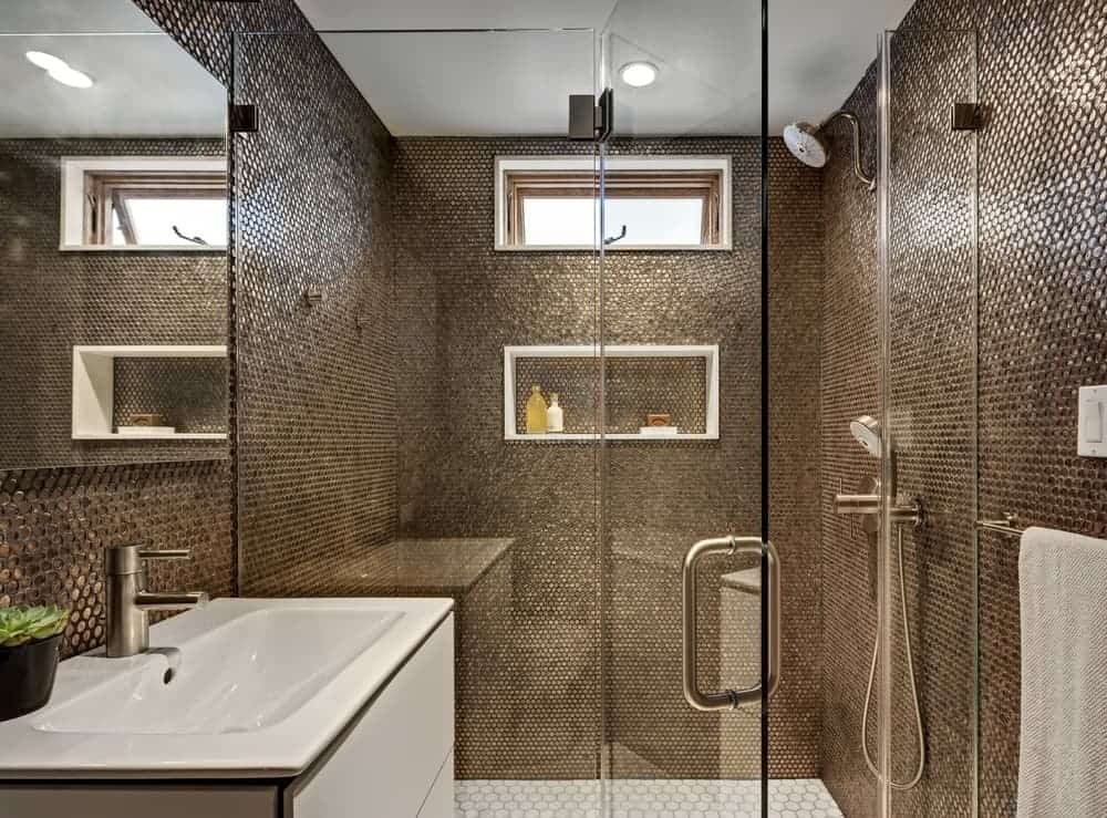 The walls of this simple bathroom are dominated by the brass-like hues of the patterned and textured walls. This provides a complex aesthetic to the simple glass enclosure of the shower area and the white modern vanity with white sink.