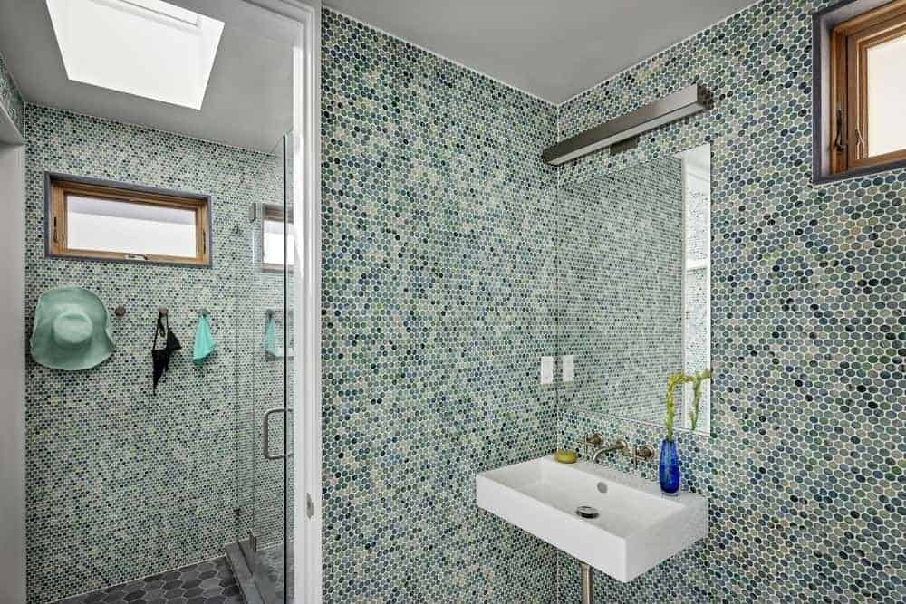 This Beach-style bathroom has a shower area through a glass door near the floating white porcelain sink paired with a frameless mirror that is topped with a modern wall-mounted lamp. All these are given a nice complex background filled with various shades of green.