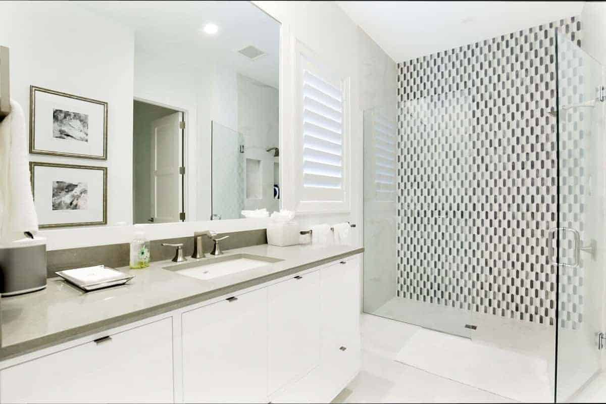 The wall tiles of the glass enclosed shower area has a complex gray pattern to it that stands out against the stark white flooring tiles and vanity complemented by the gray countertop matched with a frameless mirror mounted on the white wall.