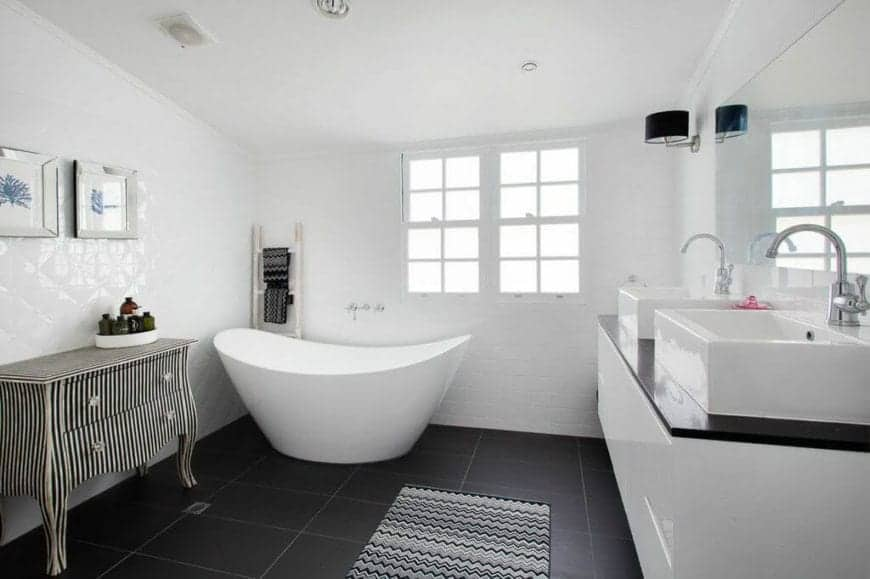 The lovely black flooring tiles of this Beach-style master bathroom provides a nice contrast to the white freestanding bathtub in the corner of white walls blending with the modern white floating vanity with two white sinks on its black countertop.