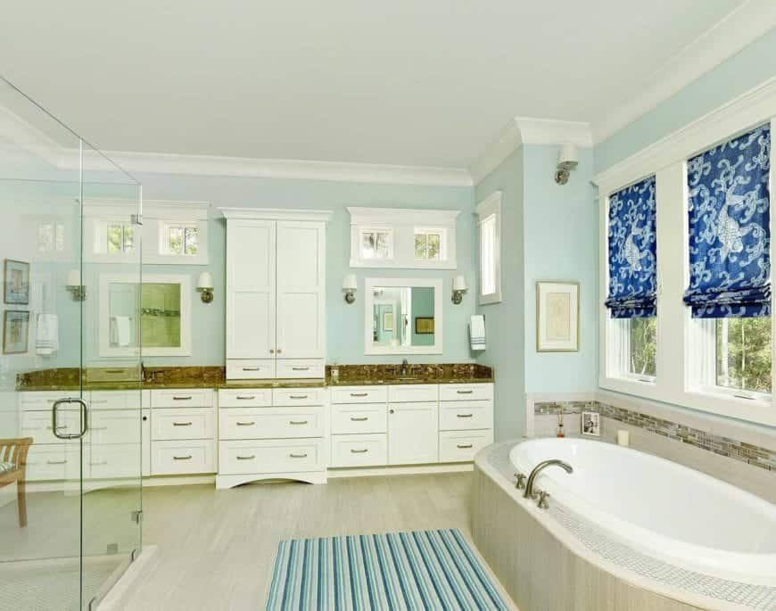 The large white wooden structure against the light green wall houses two sinks on its brown countertops topped with white-framed mirrors flanked with wall-mounted lamps and small windows matching those above the white bathtub.