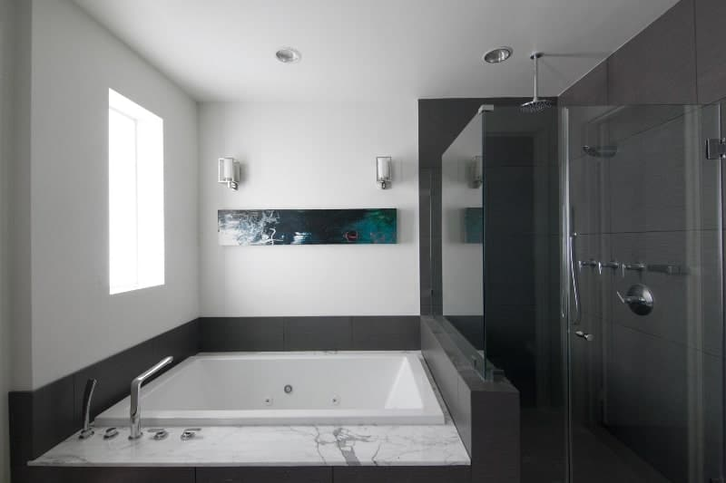 The glass enclosed shower area has black tiles on its walls and flooring blending with the housing of the square corner bathtub with a white marble countertop that matches the white walls and ceiling that has recessed lights.