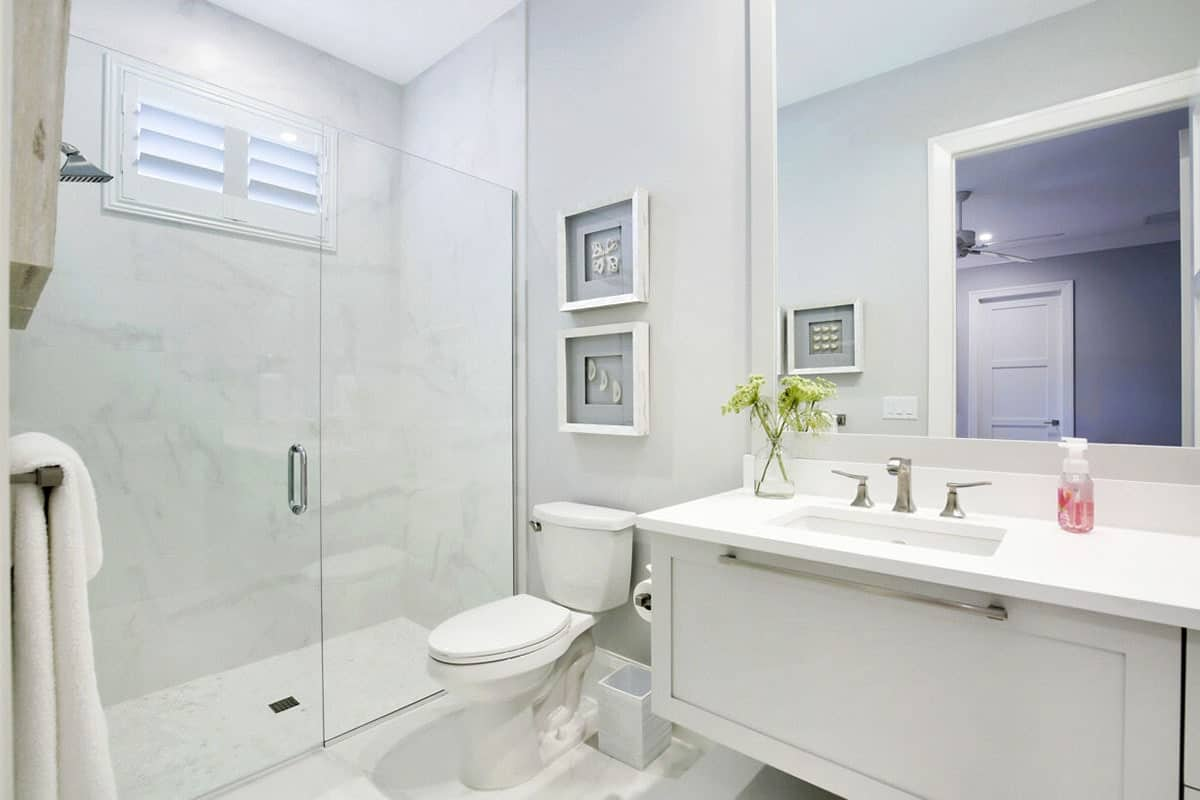 The white porcelain toilet that is topped with a couple of framed artworks is sitting in between the glass enclosed shower area and the floating white vanity that matches the aesthetic of the Beach-style bathroom.