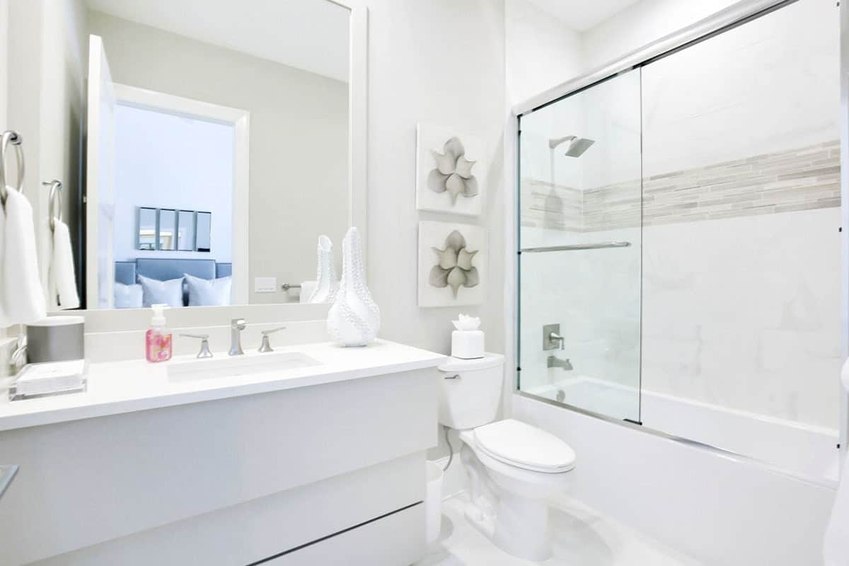 The light gray wall above the stark white toilet is adorned with two lovely gray floral paintings that matches with the row of gray tiles traversing the white walls of the shower area with fixtures matching those of the white modern vanity.