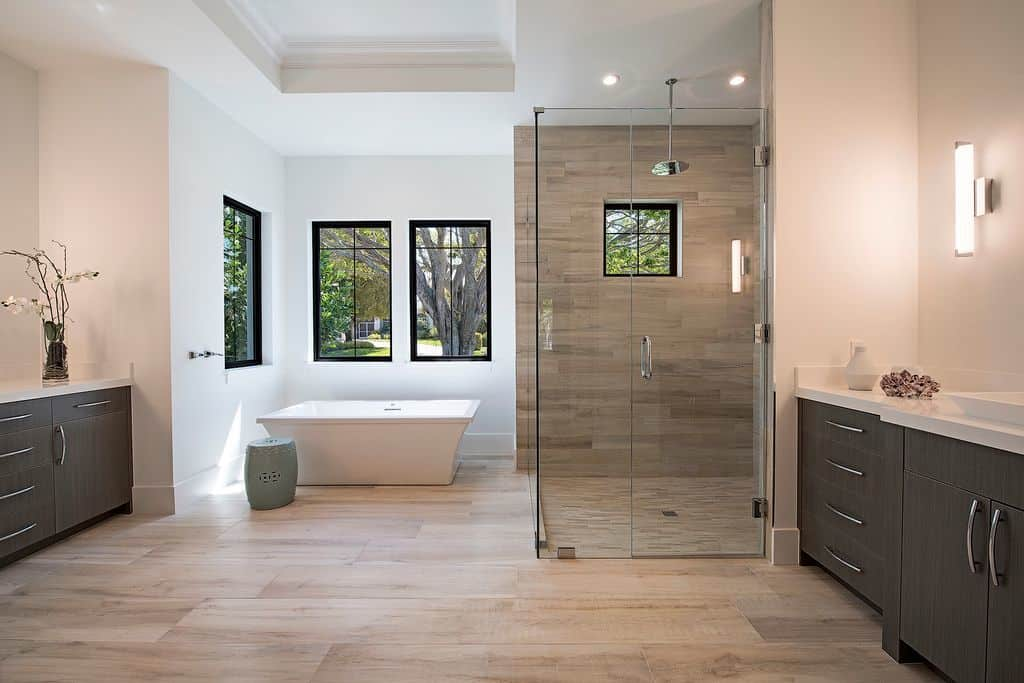 This spacious Beach-style primary bathroom has a wide beige marble flooring that goes well with the white tray ceiling and white walls warmed up by the yellow lights of the wall-mounted lamps above the dark wooden vanities.