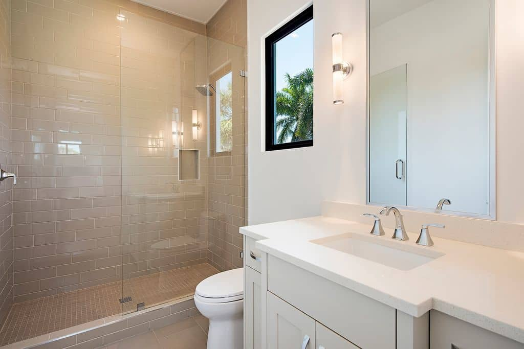 The glass enclosed shower area on the far wall has beige tiles on its walls and flooring extending to the rest of the Beach-style bathroom that has a white toilet and white modern vanity blending with the white walls adorned with modern lamps.