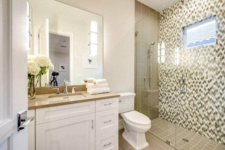 The glass-enclosed shower area has a moss green tone to it with three different kinds of tiles on its floor, and adjacent walls providing a nice complexity to the simple white vanity and white toilet against beige floor tiles.