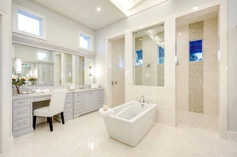 The large shower area on the far wall, that is large enough for two, has the same beige marble tiles as the flooring on its walls accented with different beige tiles to form a striped pattern with the windows. This is a nice background for the light gray wooden vanity beside the white freestanding bathtub.
