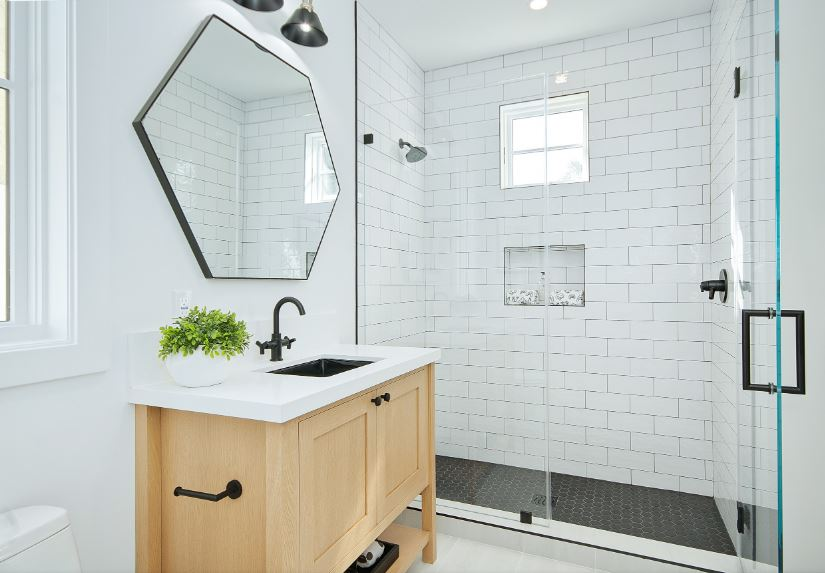 The white wall tiles of the shower area has a brick wall pattern that goes well with the wooden vanity. The whiteness of this bathroom is accented with small black details like the sink and faucet that matches with the other black fixtures of the bathroom.