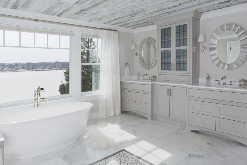 The wide glass windows above the freestanding bathtub showcases a lovely watery scenery that gives a charming accent to the simple light gray hues of the two-sink vanity with elegant round mirrors and modern wall lamps.