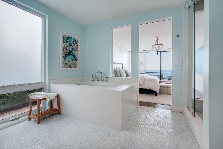 The colorful floral painting mounted on the light green wall above the bathtub provides a dash of color to the white and light gray hues of the bathtub housing and the flooring as well as the white ceiling.