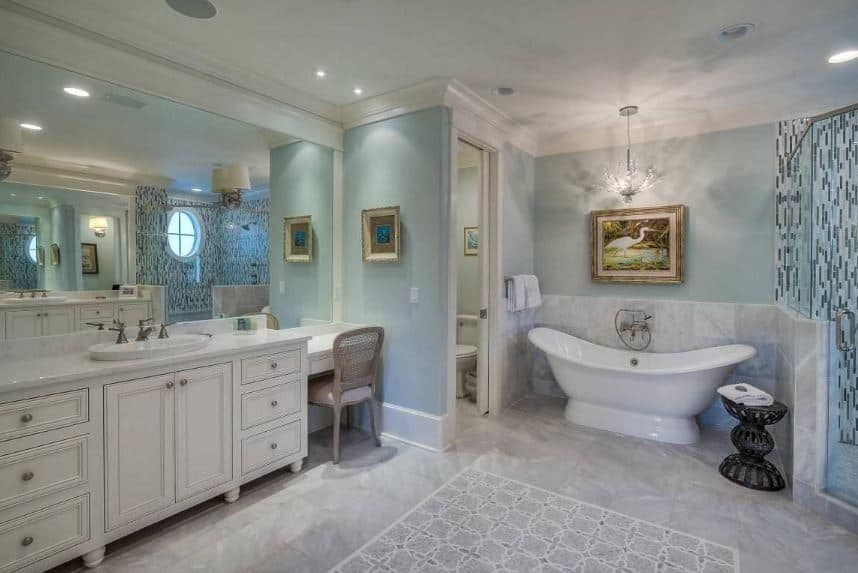 This wonderfully chic Beach-style primary bathroom has delightful light green walls adorned with a painting of a stork mounted above the freestanding bathtub in between the toilet area and the shower area reflected by the large mirror of the wooden vanity.