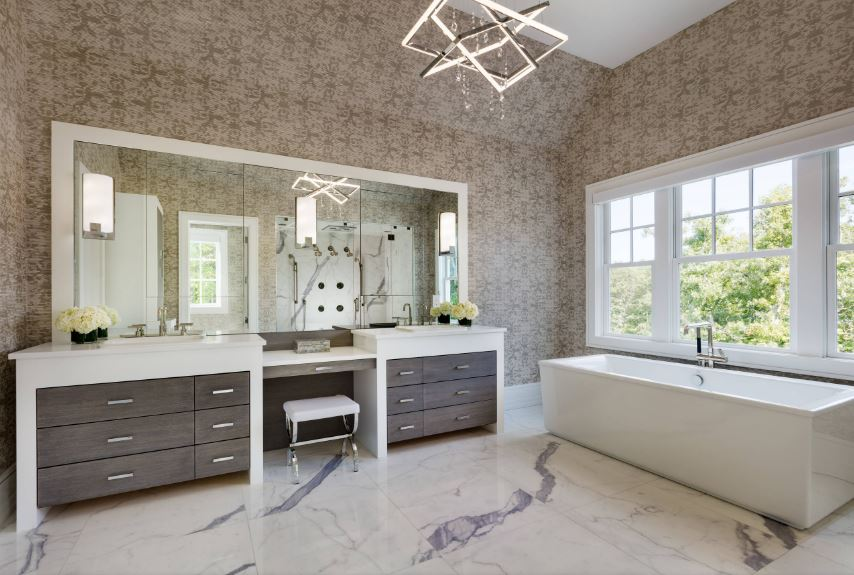 The modern geometric pendant light hanging from the white ceiling stands out against the brown patterned wallpaper that makes the white frames of the large window stand out along with the white freestanding bathtub and the white trimmings of the two-sink vanity.
