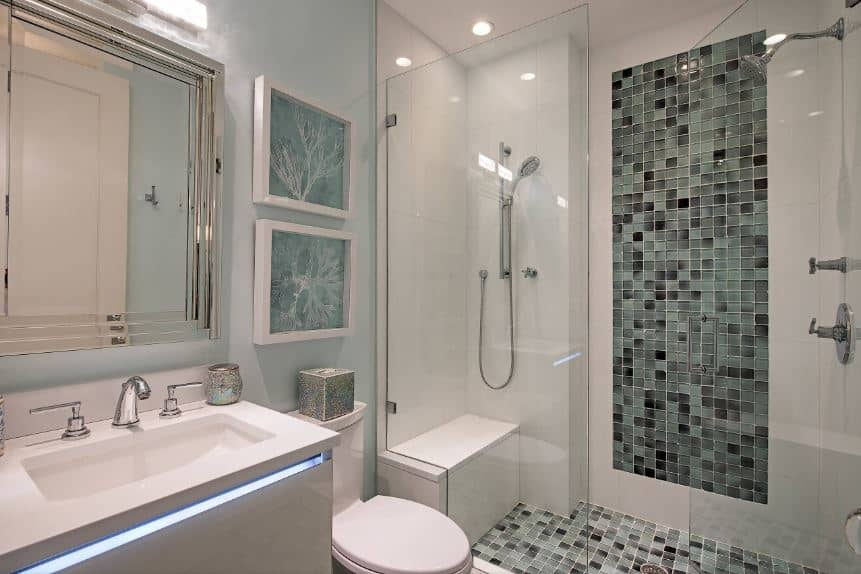 This simple Beach-style bathroom has various shades of gray on the wall and flooring of the glass-enclosed shower area beside the white toilet topped with green artworks above it beside a modern gray vanity with LED lighting.