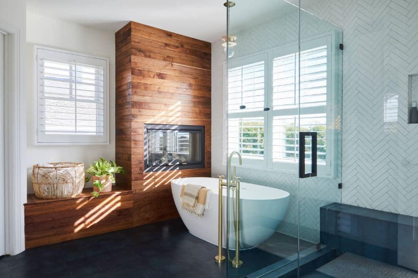 By the head of the freestanding bathtub, there is a glass enclosed fireplace that is housed in a large wooden structure that stands out against the white walls and ceiling adorned with shuttered white windows illuminating the black flooring.