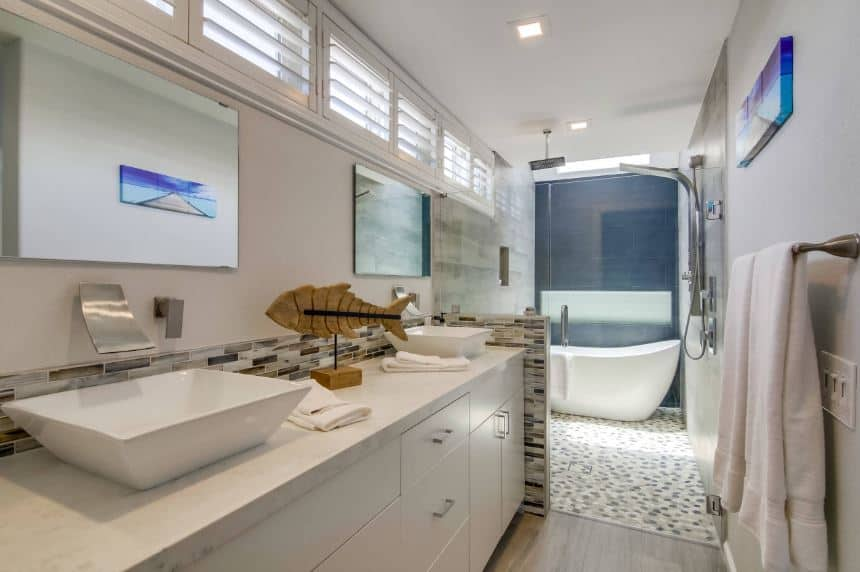 At the far end of this narrow bathroom is a white freestanding tub against a dark gray wall. This is inside a wet area along with the shower through glass doors from the two sink vanity area adorned with a wooden sculpture of a fish.