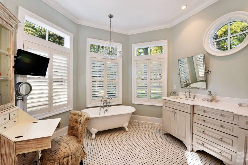 The complex patterned white flooring provides a nice background for the light gray walls dominated by white shuttered windows above the freestanding bathtub that matches the white countertop of the light gray wooden vanity.