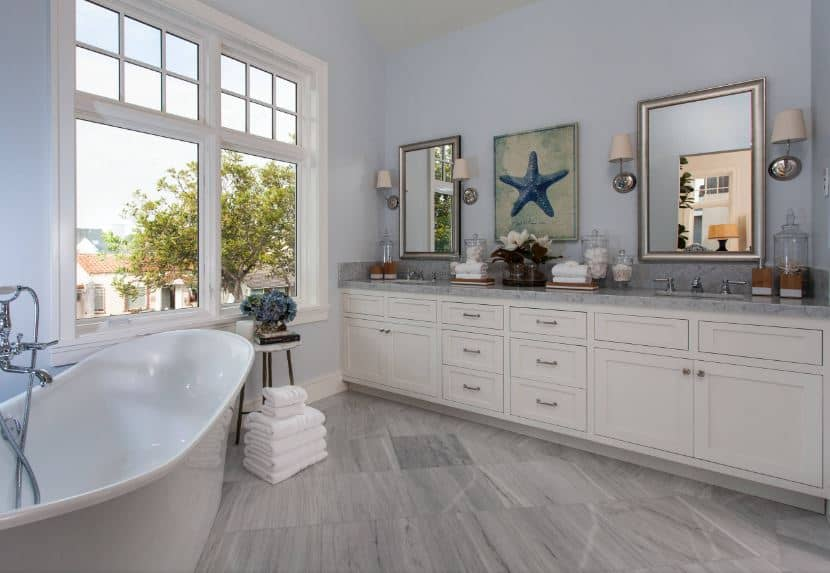 The light blue walls of this Beach-style primary bathroom are adorned with silver-framed vanity mirrors flanked with modern wall lamps above the white wooden two-sink vanity across from the freestanding bathtub by the window.