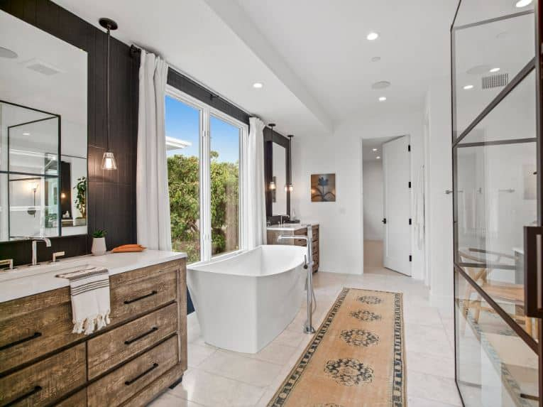 The white marble flooring tiles are adorned with a beige patterned area rug that complements the white freestanding bathtub placed beside large curtained windows that brighten up the white ceiling and black walls of the two vanities.