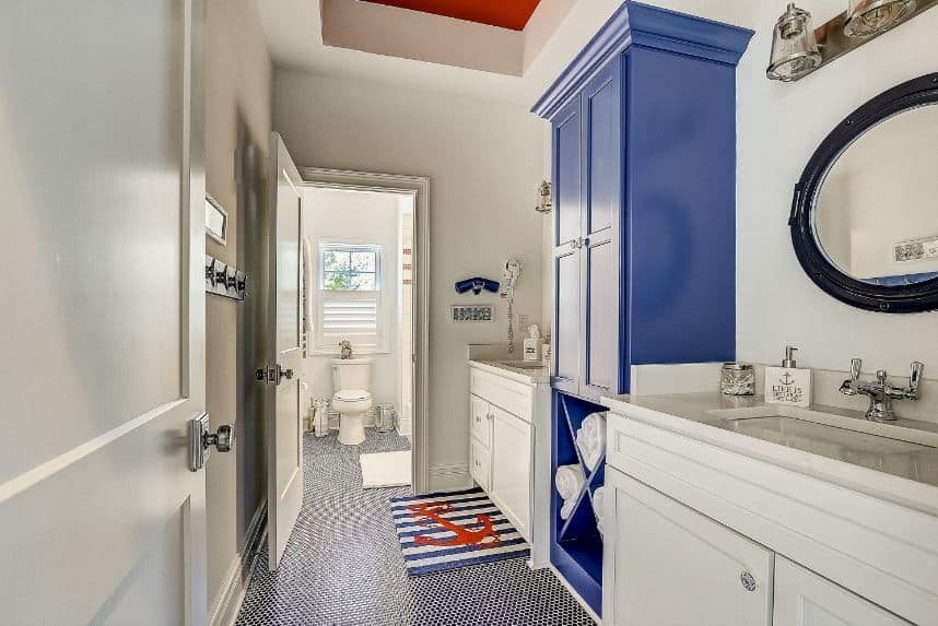 The two white wooden vanities of this bathroom are flanking a blue wooden structure that has shelves for towel storage. This is complemented by a complex flooring with small tiles that leads to the toilet area at the far end.