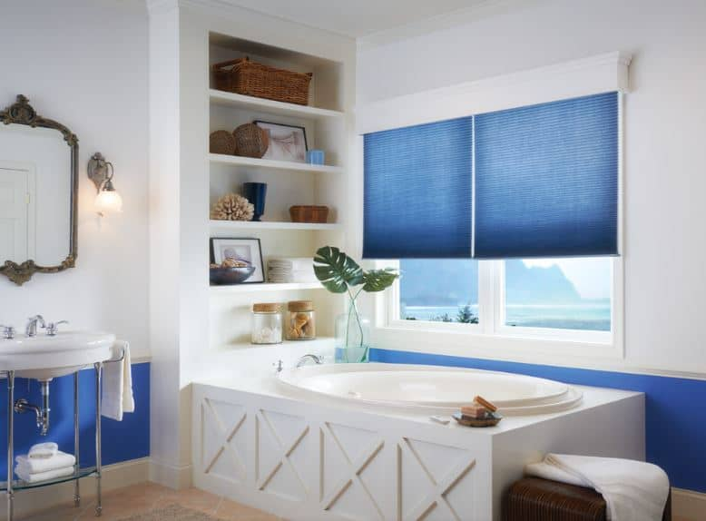 The lower part of the white walls are given a bright blue tone that matches with the blue shutters of the white windows that showcase a lovely scenery outside that bring natural lighting to the oval bathtub inlaid with white.