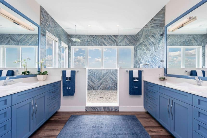 The blue wooden vanities across from each other has a matching blue area rug over the hardwood flooring that leads to the shower area on the far wall that is large enough for two within its blue patterned walls with a row of windows.