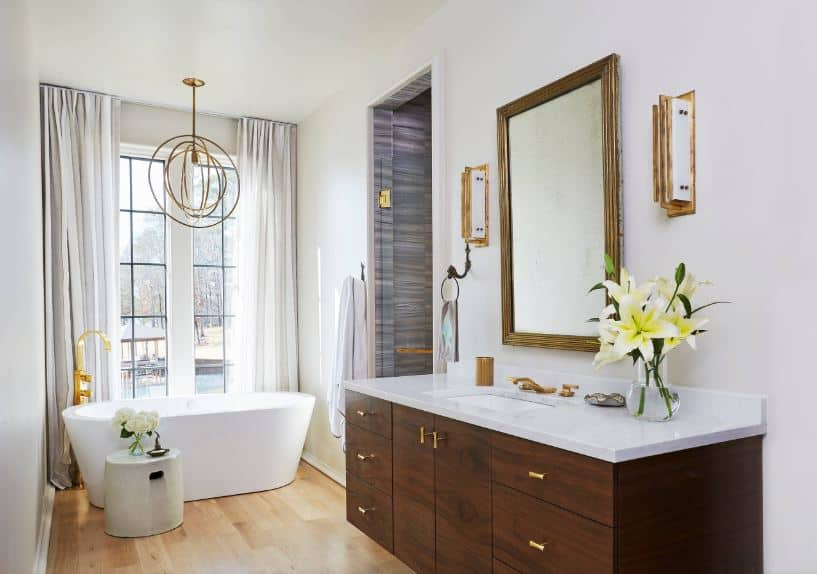 This narrow Beach-style bathroom has enough space for a freestanding bathtub at the far end by the tall curtained windows that brighten up the white walls and ceiling with an elegant brass pendant light over the bathtub.