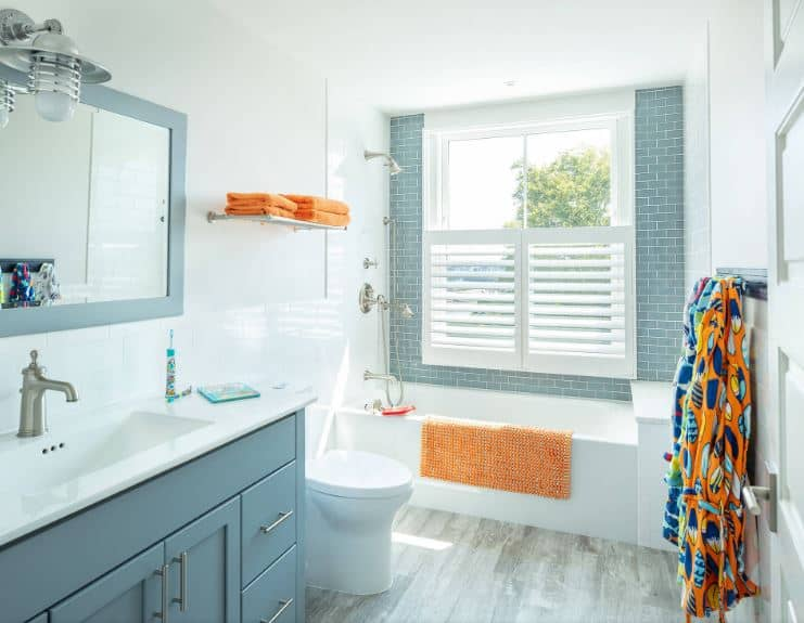 This delightful and bright bathroom has light green tiles on the wall surrounding the white shuttered windows above the bathtub that blends with the white toilet and countertop of the light gray wooden vanity with an industrial wall lamp above.
