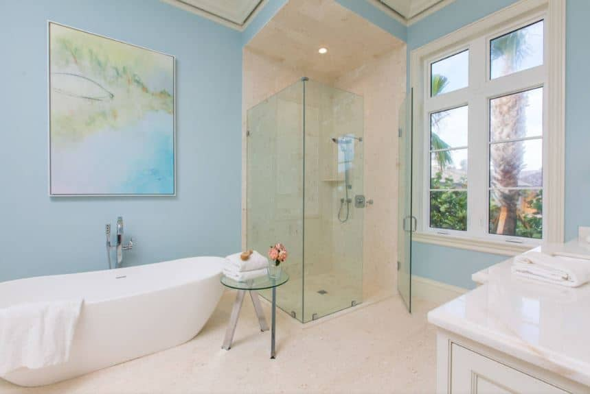 The highlight of this delightfully chic Beach-style primary bathroom is the beautiful and colorful painting mounted on the light blue wall above the freestanding bathtub that is beside the glass-enclosed shower area with beige tiles same as the flooring.