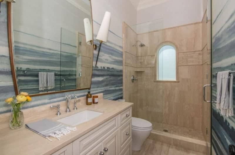 A small and narrow beach style bathroom with a beige sink counter and a walk-in shower.