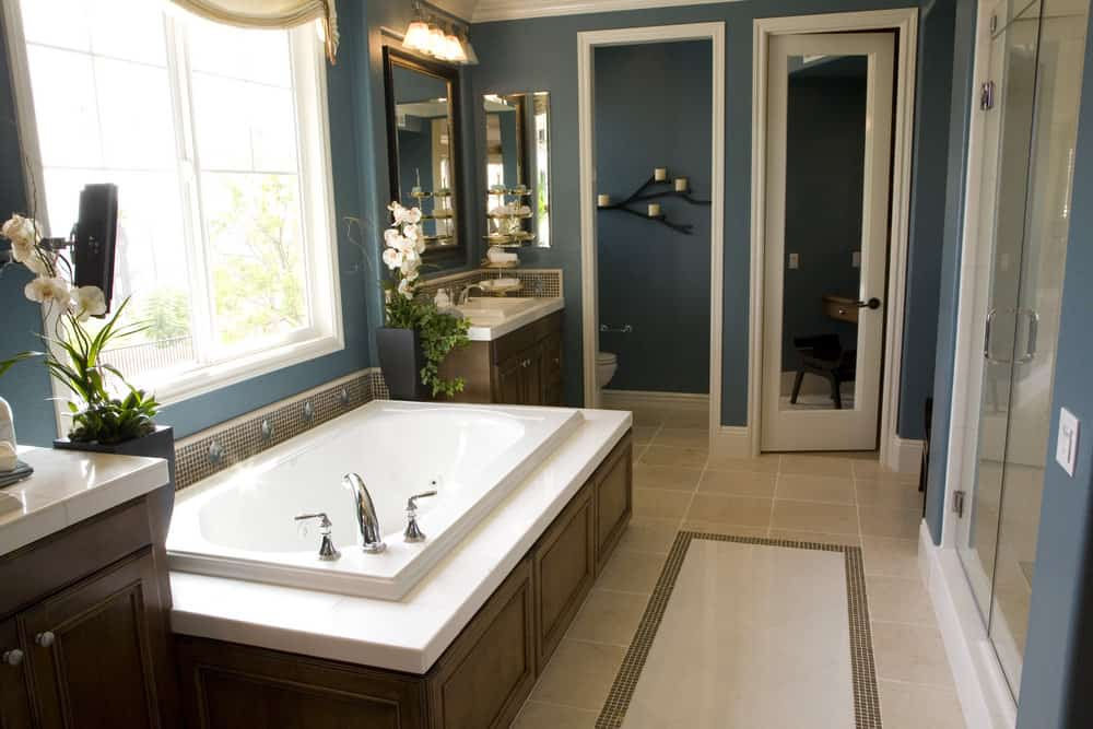 Blue master bathroom with two classy sinks and a deep soaking tub, along with a walk-in shower room and a toilet room.