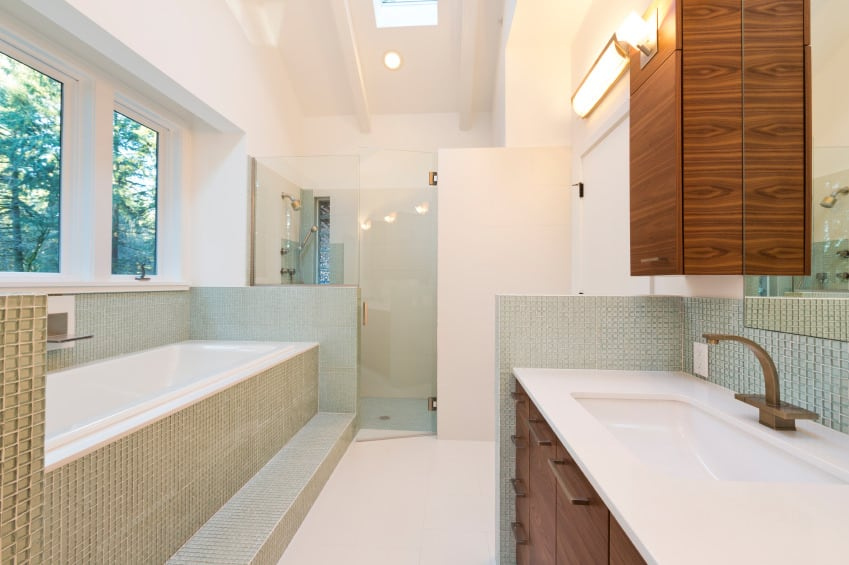 This primary bathroom offers a walk-in corner shower and a deep soaking tub under the room's tall ceiling with a skylight.
