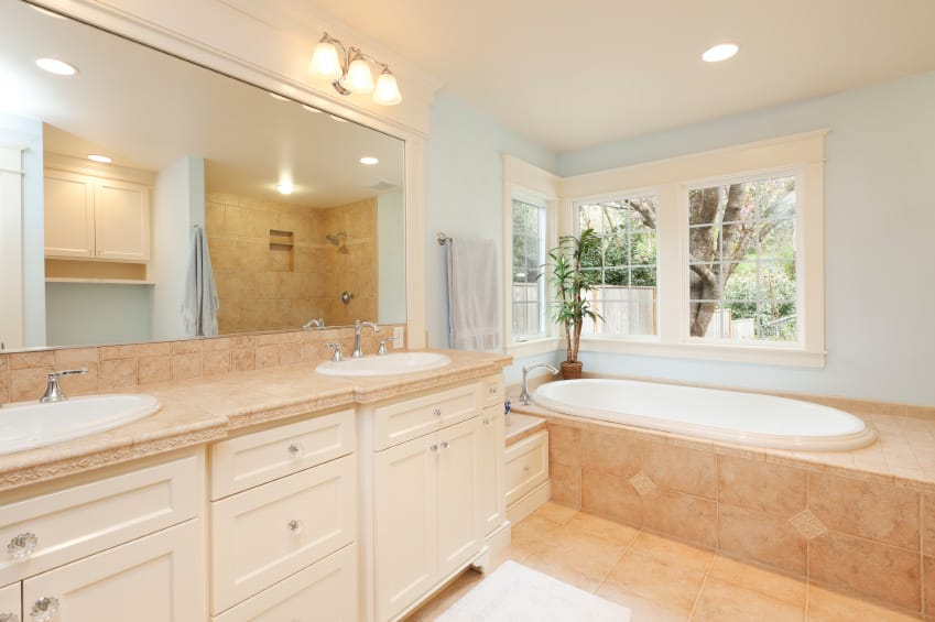A bright master bathroom with a beautiful sink counter lighted by gorgeous wall lights along with a deep soaking tub with beige tiles platform.
