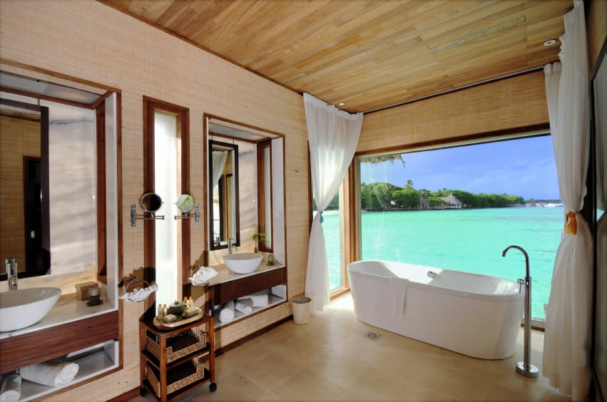 This beach style primary bathroom boasts a pair of sink counters with vessel sinks along with a freestanding tub set near the windows overlooking the breathtaking ocean view.