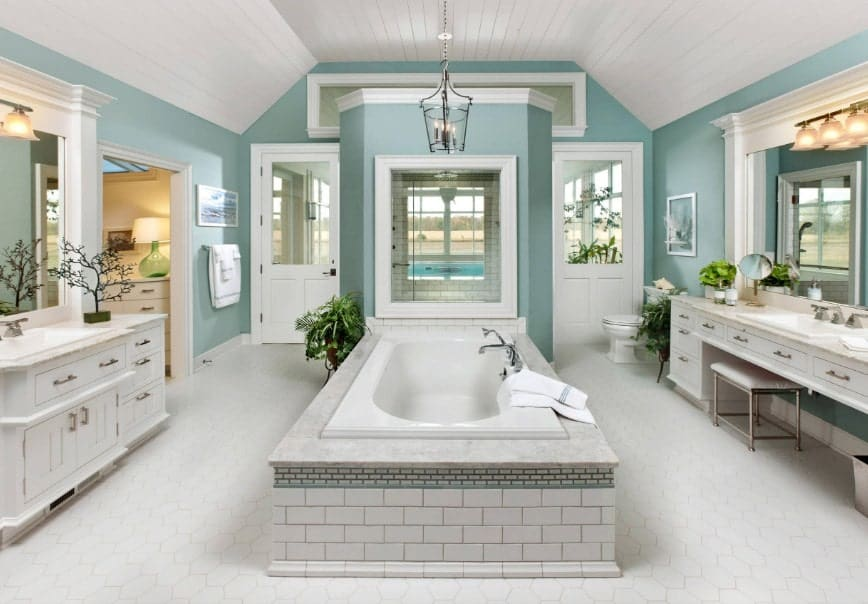 Huge beach style primary bathroom with green walls, white tiles flooring and a white wooden ceiling. The room offers two sinks, a powder desk, a deep soaking tub on the center and a walk-in shower room.