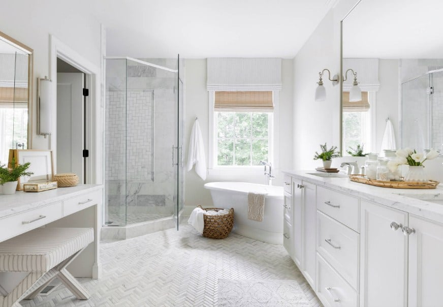 Bright beach style primary bathroom featuring herringbone-style flooring. It offers a powder desk, a freestanding tub and a corner walk-in shower.