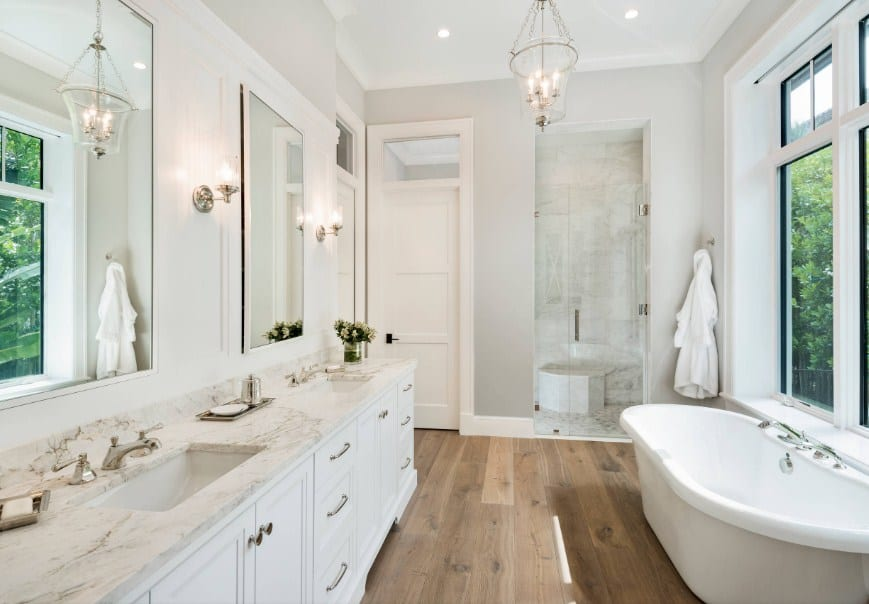 A beach style primary bathroom with hardwood floors and light gray walls. The room offers a marble sink counter with two sinks along with a freestanding tub and a walk-in shower.