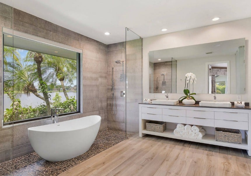 A spacious primary bathroom with a stylish shower and tub area. There's a sink counter with two vessel sinks.