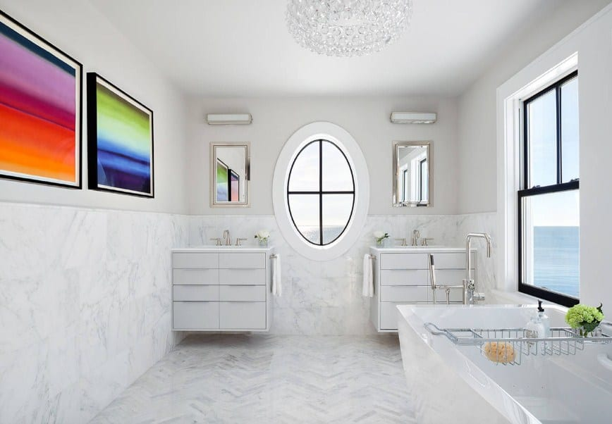 A bright beach style primary bathroom featuring colorful wall art decors along with two floating vanities with own sinks. The room is lighted by a glamorous ceiling light.