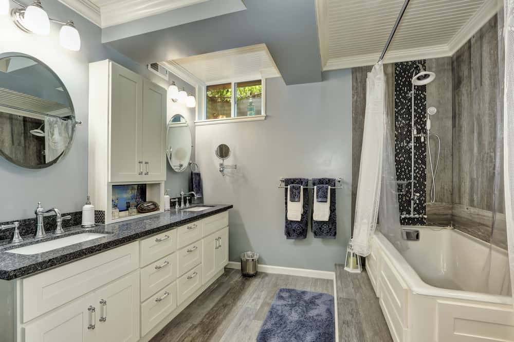Beach-style bathroom with blue walls, wall sconces, round vanity mirrors, double sink, and a drop-in tub.