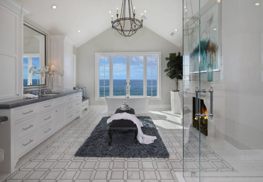 Large beach style primary bathroom with stylish tiles flooring along with a large sink counter, a large walk-in shower, a fireplace and freestanding tub near the windows with a breathtaking view of the sprawling sea.
