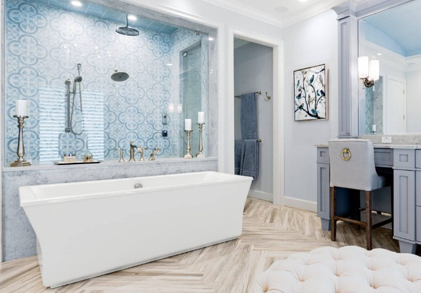 This primary bathroom boasts a beautiful shower area with glass walls. The large freestanding soaking tub is set just outside the shower room.